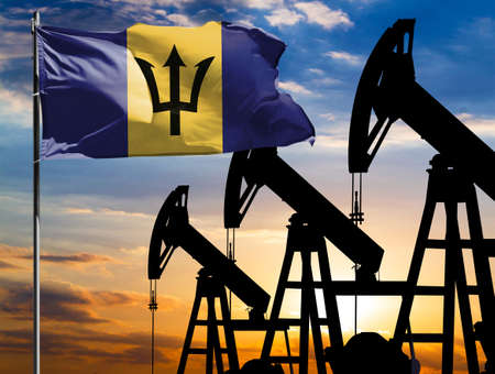 Oil rigs against the backdrop of the colorful sky and a flagpole with the flag of Barbados. The concept of oil production, minerals, development of new deposits.