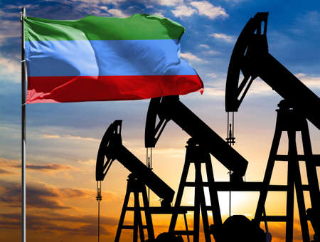 Oil rigs against the backdrop of the colorful sky and a flagpole with the flag of Dagestan. The concept of oil production, minerals, development of new deposits.