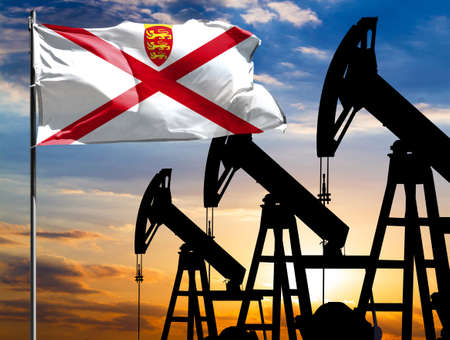 Oil rigs against the backdrop of the colorful sky and a flagpole with the flag of Jersey. The concept of oil production, minerals, development of new deposits.