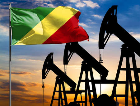 Oil rigs against the backdrop of the colorful sky and a flagpole with the flag of Congo, Republic. The concept of oil production, minerals, development of new deposits.