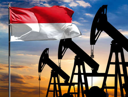 Oil rigs against the backdrop of the colorful sky and a flagpole with the flag of Monaco. The concept of oil production, minerals, development of new deposits.