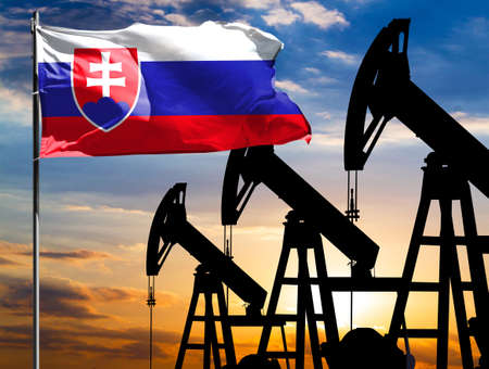 Oil rigs against the backdrop of the colorful sky and a flagpole with the flag of Slovakia. The concept of oil production, minerals, development of new deposits.