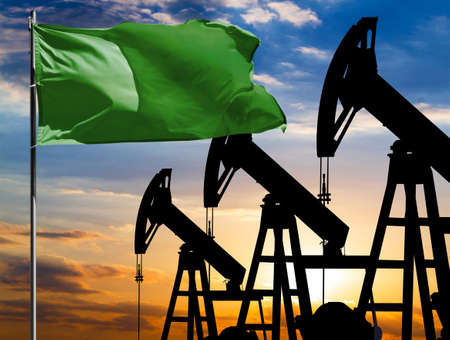 Oil rigs against the backdrop of the colorful sky and a flagpole with the flag of Libya. The concept of oil production, minerals, development of new deposits. 免版税图像