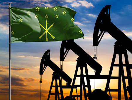 Oil rigs against the backdrop of the colorful sky and a flagpole with the flag of Adygea. The concept of oil production, minerals, development of new deposits.