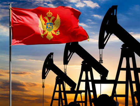 Oil rigs against the backdrop of the colorful sky and a flagpole with the flag of Montenegro. The concept of oil production, minerals, development of new deposits.
