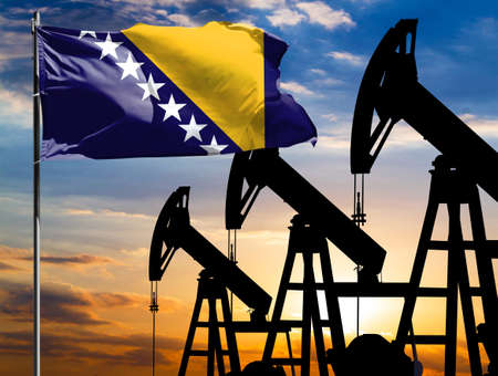 Oil rigs against the backdrop of the colorful sky and a flagpole with the flag of Bosnia and Herzegovina. The concept of oil production, minerals, development of new deposits. 免版税图像