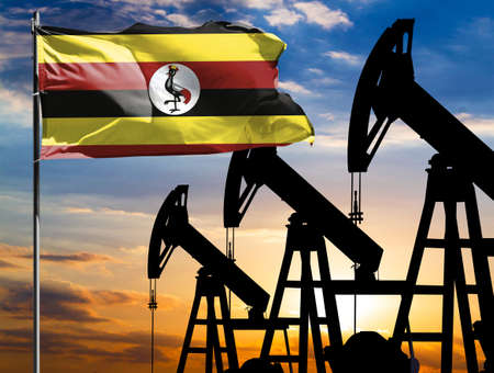 Oil rigs against the backdrop of the colorful sky and a flagpole with the flag of Uganda. The concept of oil production, minerals, development of new deposits.