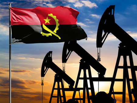 Oil rigs against the backdrop of the colorful sky and a flagpole with the flag of Angola. The concept of oil production, minerals, development of new deposits.