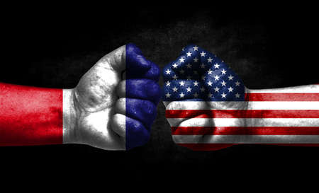 The concept of the confrontation of peoples. The two fists are opposite each other. The hands are painted in the colors of the flags of the countries. America versus France