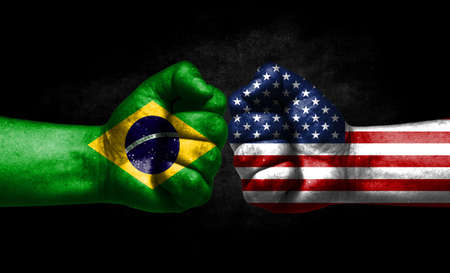 The concept of the confrontation of peoples. The two fists are opposite each other. The hands are painted in the colors of the flags of the countries. America versus brazil Banco de Imagens