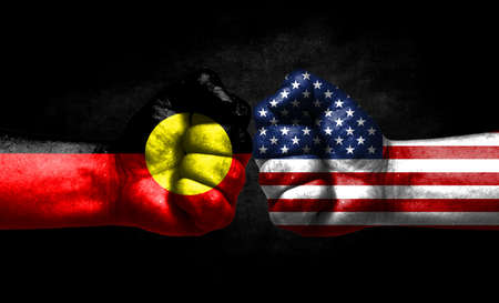The concept of the confrontation of peoples. The two fists are opposite each other. The hands are painted in the colors of the flags of the countries. America versus Australian Aboriginal Banco de Imagens