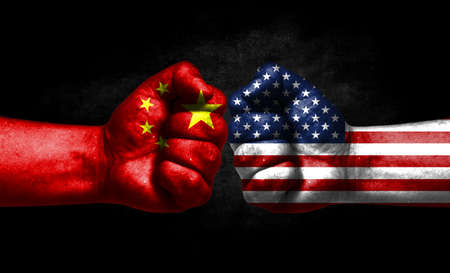 The concept of the confrontation of peoples. The two fists are opposite each other. The hands are painted in the colors of the flags of the countries. America versus china Banco de Imagens
