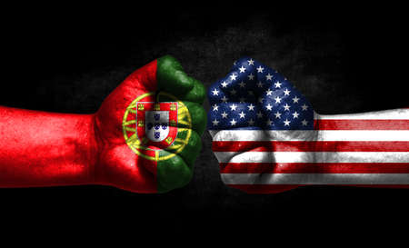 The concept of the confrontation of peoples. The two fists are opposite each other. The hands are painted in the colors of the flags of the countries. America versus Portugal