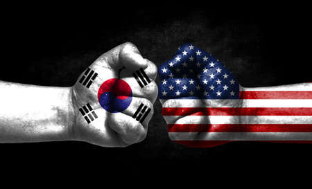 The concept of the confrontation of peoples. The two fists are opposite each other. The hands are painted in the colors of the flags of the countries. America versus South Korea Banco de Imagens