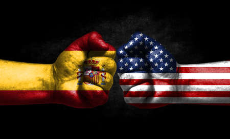 The concept of the confrontation of peoples. The two fists are opposite each other. The hands are painted in the colors of the flags of the countries. America versus spain