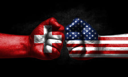 The concept of the confrontation of peoples. The two fists are opposite each other. The hands are painted in the colors of the flags of the countries. America versus Switzerland