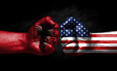 The concept of the confrontation of peoples. The two fists are opposite each other. The hands are painted in the colors of the flags of the countries. America versus albania