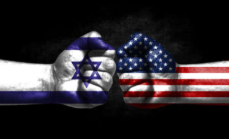 The concept of the confrontation of peoples. The two fists are opposite each other. The hands are painted in the colors of the flags of the countries. America versus israel