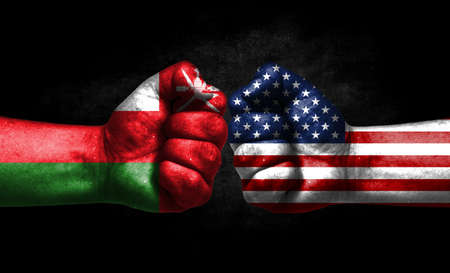 The concept of the confrontation of peoples. The two fists are opposite each other. The hands are painted in the colors of the flags of the countries. America versus oman