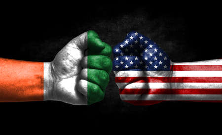 The concept of the confrontation of peoples. The two fists are opposite each other. The hands are painted in the colors of the flags of the countries. America versus Ireland