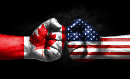 The concept of the confrontation of peoples. The two fists are opposite each other. The hands are painted in the colors of the flags of the countries. America versus Canada Banco de Imagens