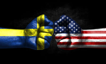 The concept of the confrontation of peoples. The two fists are opposite each other. The hands are painted in the colors of the flags of the countries. America versus Sweden