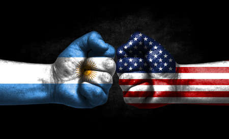 The concept of the confrontation of peoples. The two fists are opposite each other. The hands are painted in the colors of the flags of the countries. America versus Argentina