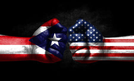 The concept of the confrontation of peoples. The two fists are opposite each other. The hands are painted in the colors of the flags of the countries. America versus puerto rico