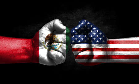 The concept of the confrontation of peoples. The two fists are opposite each other. The hands are painted in the colors of the flags of the countries. America versus mexico