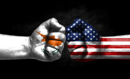 The concept of the confrontation of peoples. The two fists are opposite each other. The hands are painted in the colors of the flags of the countries. America versus Cyprus Banco de Imagens