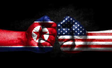 The concept of the confrontation of peoples. The two fists are opposite each other. The hands are painted in the colors of the flags of the countries. America versus North Korea Banco de Imagens