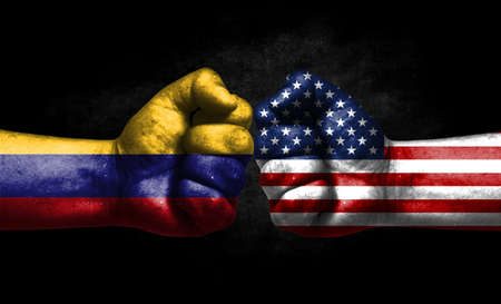 The concept of the confrontation of peoples. The two fists are opposite each other. The hands are painted in the colors of the flags of the countries. America versus colombia