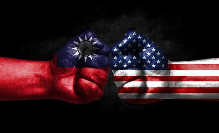 The concept of the confrontation of peoples. The two fists are opposite each other. The hands are painted in the colors of the flags of the countries. America versus Taiwan Banco de Imagens