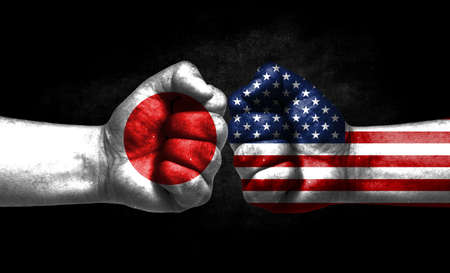 The concept of the confrontation of peoples. The two fists are opposite each other. The hands are painted in the colors of the flags of the countries. America versus japan Banco de Imagens