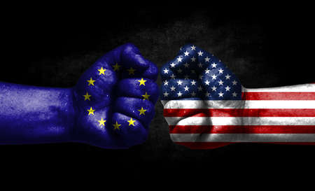 The concept of the confrontation of peoples. The two fists are opposite each other. The hands are painted in the colors of the flags of the countries. America versus European Union