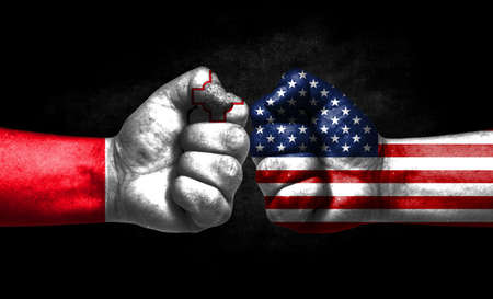 The concept of the confrontation of peoples. The two fists are opposite each other. The hands are painted in the colors of the flags of the countries. America versus Malta Banco de Imagens