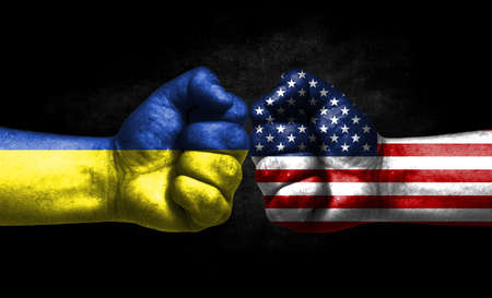 The concept of the confrontation of peoples. The two fists are opposite each other. The hands are painted in the colors of the flags of the countries. America versus Ukraine