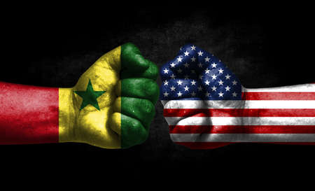 The concept of the confrontation of peoples. The two fists are opposite each other. The hands are painted in the colors of the flags of the countries. America versus senegal