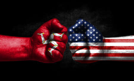 The concept of the confrontation of peoples. The two fists are opposite each other. The hands are painted in the colors of the flags of the countries. America versus isle of man