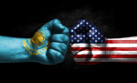 The concept of the confrontation of peoples. The two fists are opposite each other. The hands are painted in the colors of the flags of the countries. America versus Kazakhstan