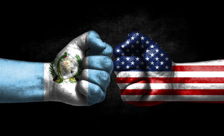 The concept of the confrontation of peoples. The two fists are opposite each other. The hands are painted in the colors of the flags of the countries. America versus guatemala