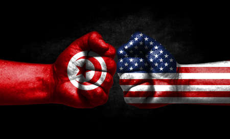 The concept of the confrontation of peoples. The two fists are opposite each other. The hands are painted in the colors of the flags of the countries. America versus Tunisia