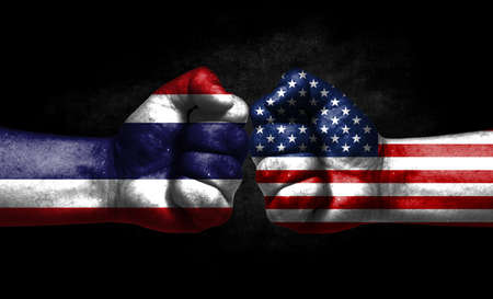 The concept of the confrontation of peoples. The two fists are opposite each other. The hands are painted in the colors of the flags of the countries. America versus thailand Banco de Imagens