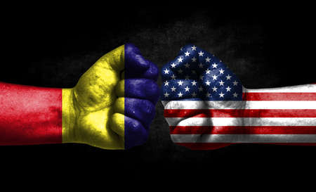The concept of the confrontation of peoples. The two fists are opposite each other. The hands are painted in the colors of the flags of the countries. America versus Romania