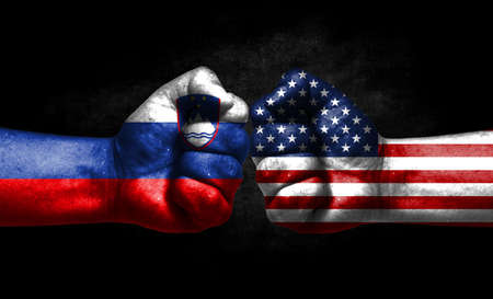 The concept of the confrontation of peoples. The two fists are opposite each other. The hands are painted in the colors of the flags of the countries. America versus slovenia Banco de Imagens