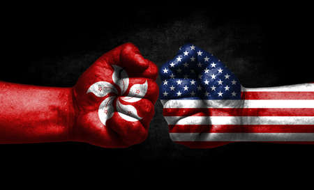 The concept of the confrontation of peoples. The two fists are opposite each other. The hands are painted in the colors of the flags of the countries. America versus Hong Kong Banco de Imagens