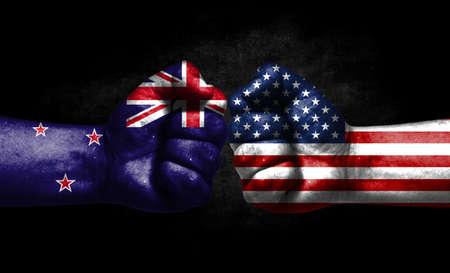The concept of the confrontation of peoples. The two fists are opposite each other. The hands are painted in the colors of the flags of the countries. America versus New Zealand