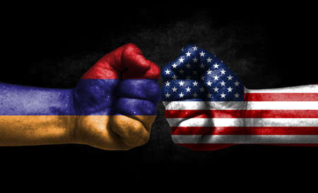 The concept of the confrontation of peoples. The two fists are opposite each other. The hands are painted in the colors of the flags of the countries. America versus Armenia