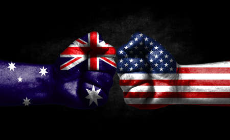 The concept of the confrontation of peoples. The two fists are opposite each other. The hands are painted in the colors of the flags of the countries. America versus Australia