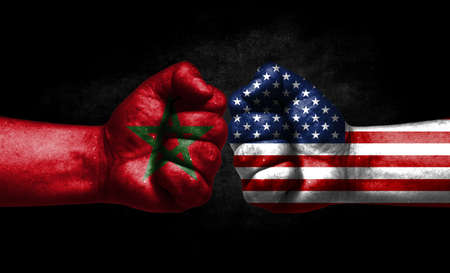 The concept of the confrontation of peoples. The two fists are opposite each other. The hands are painted in the colors of the flags of the countries. America versus morocco